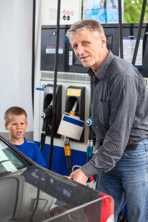 Mature man with son refueling vehicle with gasoline photo