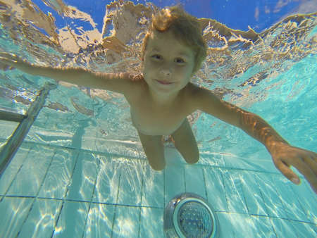 wet: Little child swimming under water in pool Stock Photo