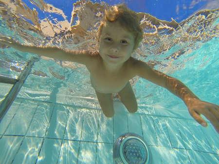 umida: Nuoto bambino piccolo sotto l'acqua in piscina