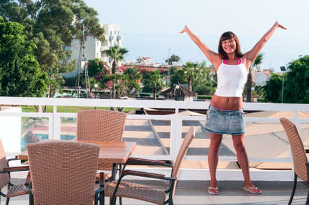 Beautiful young woman standing hands up on terrace of house photo