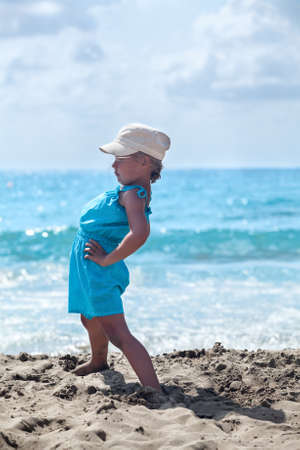 Young girl making exercising on the sandy sea beach photo