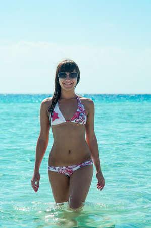 joyous: Joyous slim woman in bikini standing in water with sunglasses