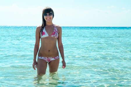 joyous: Joyous slim woman in bikini standing in water and enjoying the sun. Copyspace