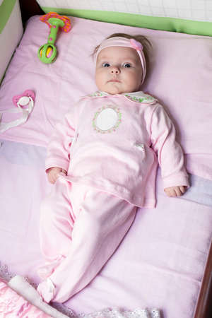 Newborn baby girl is laying in bed and wearing with pink clothes photo