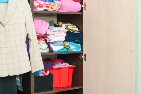 Various color clothes are organized at shelves in open wardrobe photo