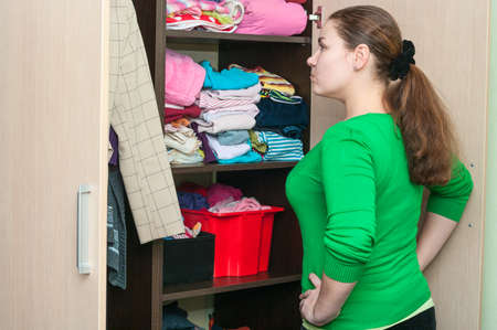 Young caucasian woman in the wardrobe selecting things for wear  photo