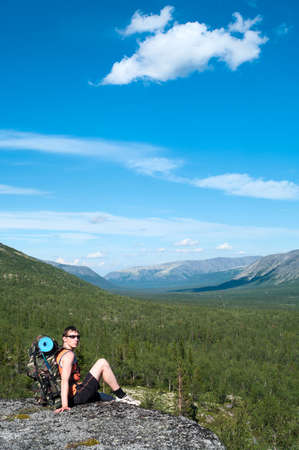 Man hiker with backpack sitting on top and looking at camera photo