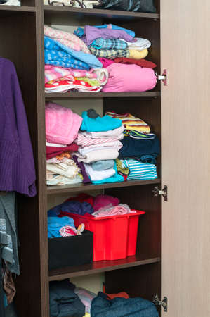Various color clothes at shelves in wardrobe photo