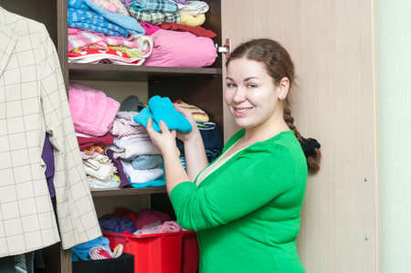 Young woman organizing clothes in the wardrobe closet at home photo