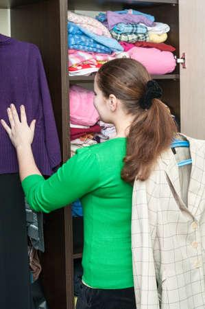 Blanke vrouw in de voorkant van georganiseerde kast thuis Stockfoto