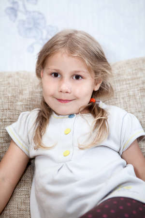 five years old: Little Caucasian girl with blond hair sitting on the couch
