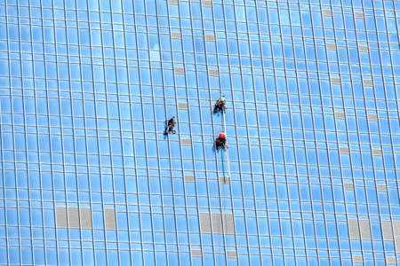 Industrial climbers working on mirror building facade Stock Photo