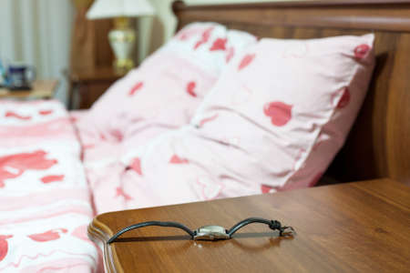 Wristwatch on the bedside cabinet in the bedroom next to the bed Stock Photo - 24143976