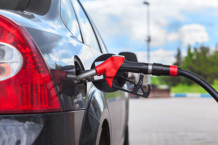 refueling: Refueling vehicle with gasoline at city gas station Stock Photo