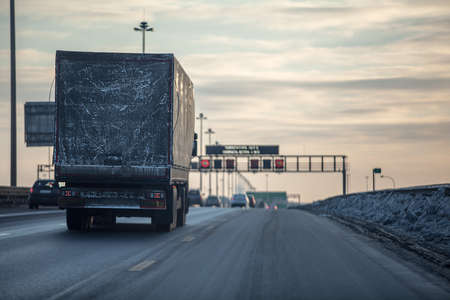 Truck on dirty winter ring road in the evening. photo