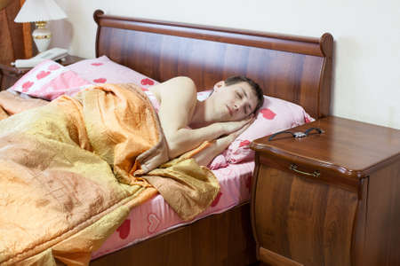 Sleeping Caucasian man in the bed. Early morning. Watch on the table photo
