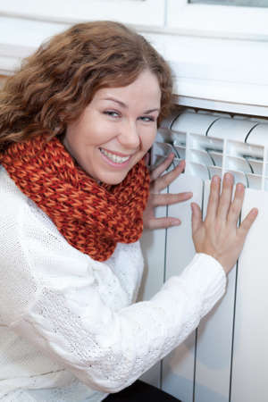 calorifer: Happy smiling woman touching warm central heating convector