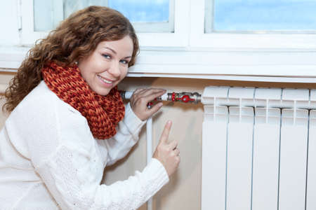 Happy woman gesturing when controling thermostat on central heating radiator photo