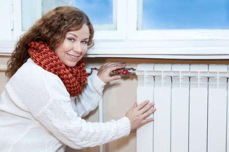 Vrouw in warme kleren controleren van de temperatuur van de radiator in de binnenlandse kamer