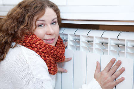 heat register: Young woman leaning to central heating convector for warming hands