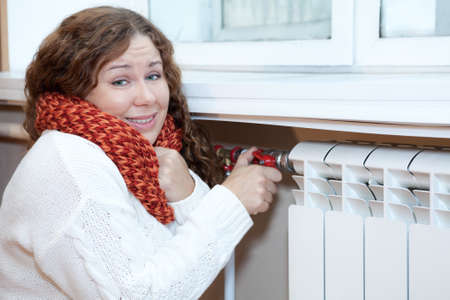 Young woman feels cold when turning thermostat of central heating convector photo