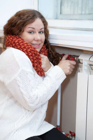 heat register: Smiling woman turning thermostat on central heating radiator