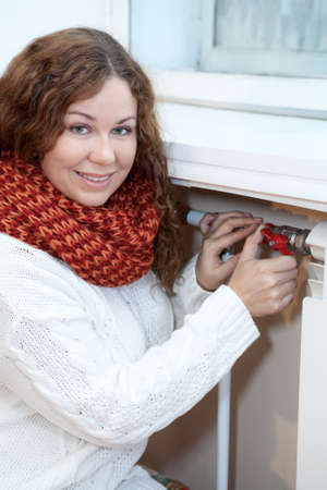 calorifer: Woman controling the temperature of heating radiator in domestic room