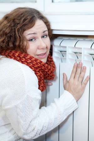 calorifer: Young woman feels cold sitting near central heating convector