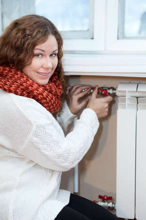 calorifer: Woman in warm clothes controling the temperature of heating radiator in domestic room