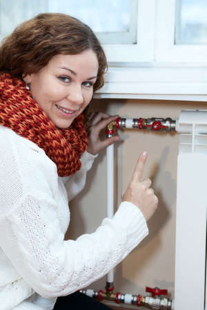 calorifer: Smiling woman gesturing when turning thermostat on central heating radiator Stock Photo
