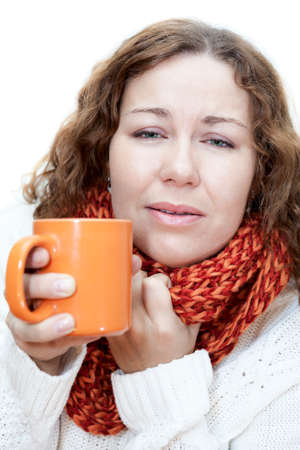 tremble: Young illness woman drinking tea with wrapping scarf on neck Stock Photo