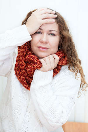 Illness woman in wool scarf with headache holding hands behind her head photo