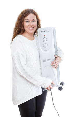 calorifer: Woman holding electric oil radiator in hands isolated on white background