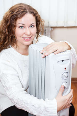 calorifer: Woman embracing radiator trying to heat up in domestic room