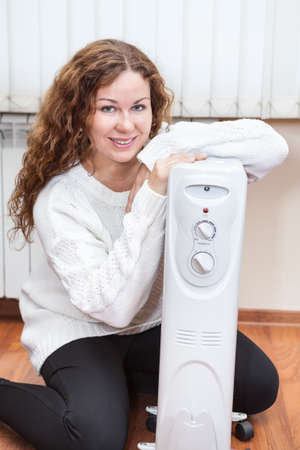 heat register: Portrait of long-haired curly woman near oil heater at her home
