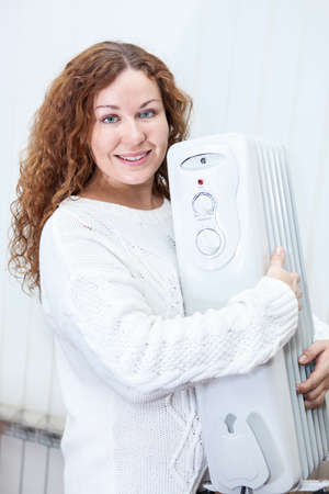 calorifer: Woman holding new buying radiator in hands