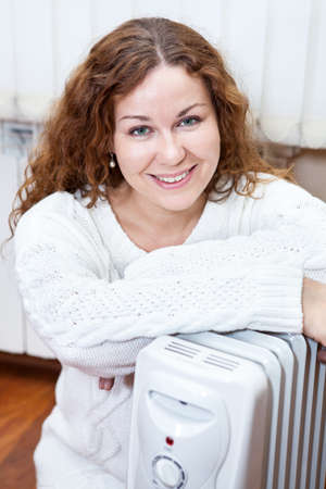 calorifer: Happy smiling woman sitting on floor with oil electric radiator