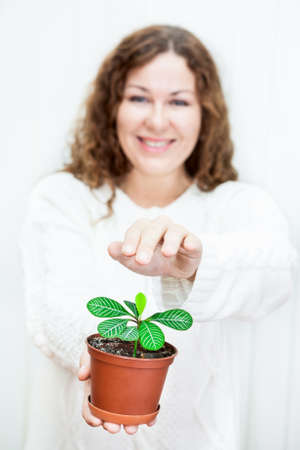 Young positive woman covering green plant by hands photo