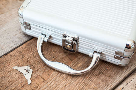 Steel closed suitcase with keys on wooden floor photo