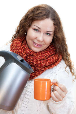 Pretty woman pouring hot water from the kettle into a cup, isolated on white  photo