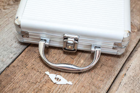 bribe: Aluminum closed suitcase with keys on wooden floor