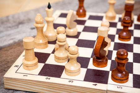 Chess pieces on wooden board table photo