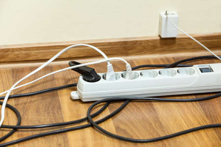 electrical appliances: Many electrical cords connected to extension block on floor