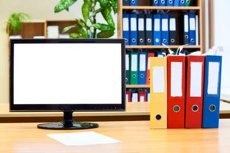 Geïsoleerde beeldscherm en gekleurde mappen voor papieren op tafel Stockfoto