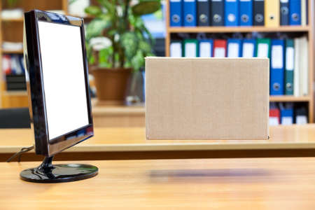 Cardboard box hanging in front of isolated white screen computer monitor Stock Photo - 24426097