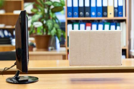 ship parcel: Big carton box hanging in front of computer monitor screen
