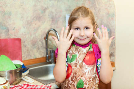 Little girl shows hands after washing dishes photo