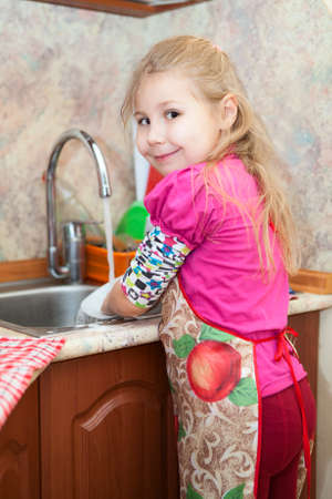 Caucasian pretty girl in the kitchen washing dishes photo
