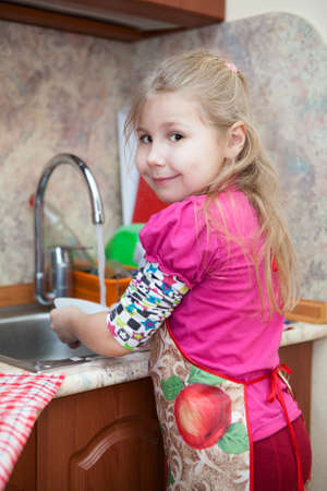 Little girl in the kitchen washing dishes photo