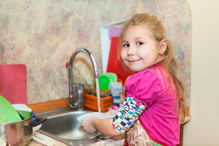 Small girl in the kitchen washing dishes, copyspace photo
